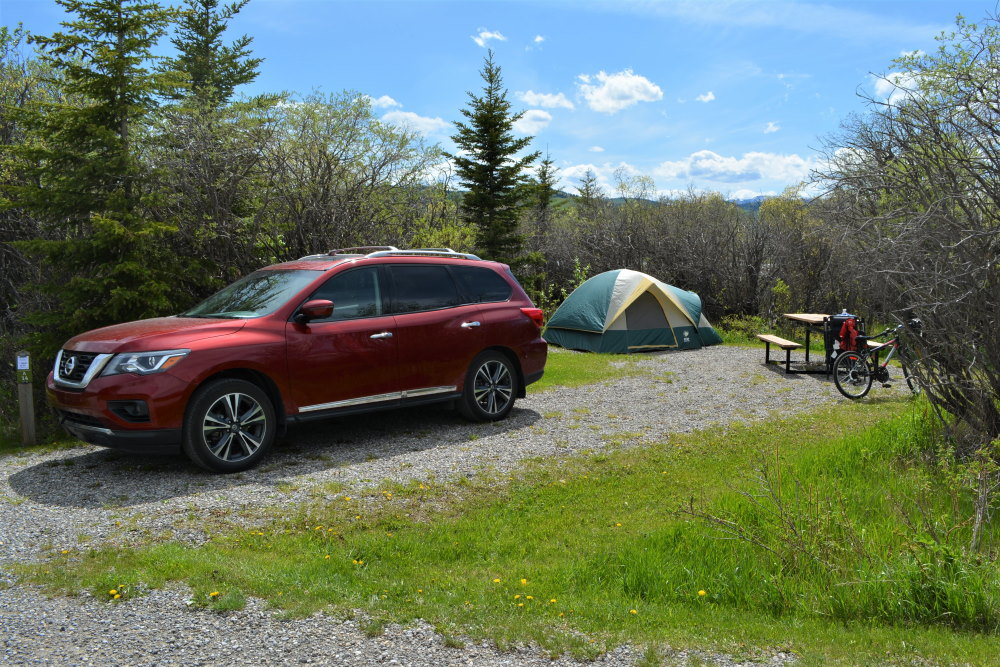 Nissan Pathfinder and tent set up on a gravel campsite