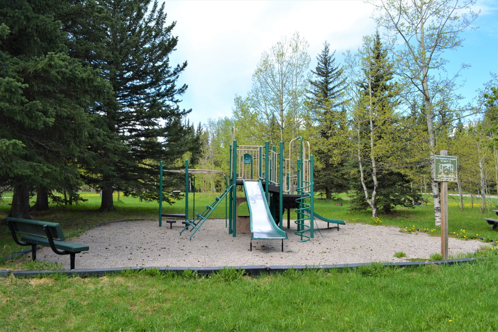 Green metal playground with slide and climbing aparatus