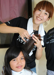 Everybody smiling at the HASAMI NO CHIKARA PROJECT, both the children and hairdressers.