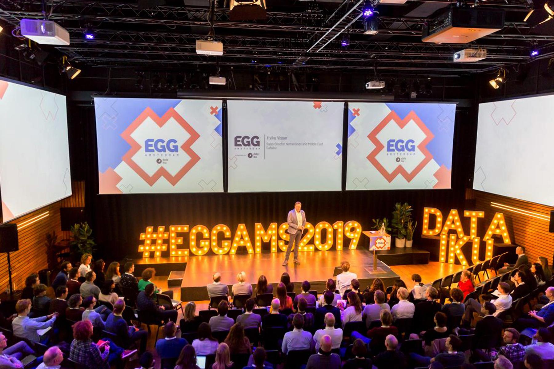 Dit is een afbeelding van de openingsfilm of kickoff van EGG Amsterdam 2019 #EGGAMS2019 dat in Pakhuis de Zwijger werd gehouden. We zien Hylke Visser het publiek aanspreken. Hij staat voor de videoschermen met daarop de huisstijl van EGG Amsterdam, bestaande uit drie Amsterdamse kruizen en blauwe of roze logo van EGG Amsterdam. Daaronder het logo in donkerblauw van Dataiku. Met mooie lampen in houten frames lezen we #EGGAMS2019. De stijl van EGG Amsterdam is volledig ontwikkeld door Activates merkversterkend reclamebureau uit Sassenheim in opdracht van Dataiku en Karin Heppener van Heppener makes it happen!