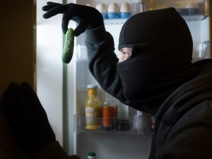 Thief. Man in black mask with a cucumber.