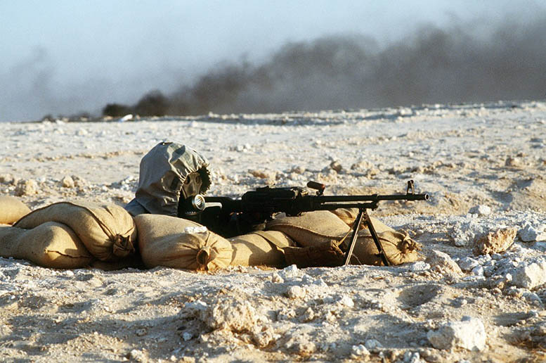 A Syrian soldier aims a 7.62mm PKM light machine gun from his position in a foxhole during a firepower demonstration, part of Operation Desert Shield. The soldier is wearing a nuclear-biological-chemical warfare mask