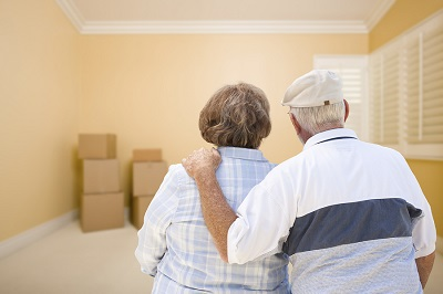 Hugging Senior Couple In Room Looking at Moving Boxes on the Florida