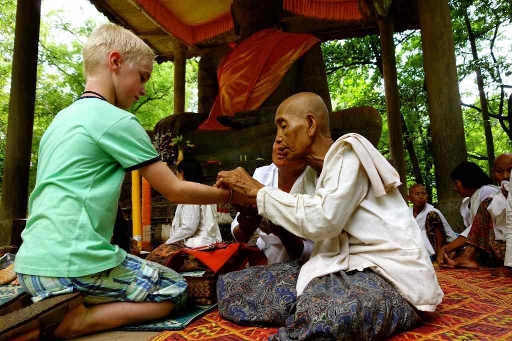 Son getting bracelet from female monks