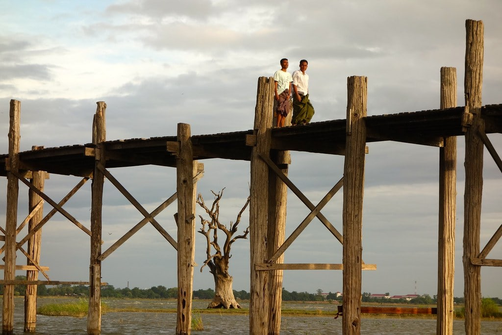 Men walking wooden bridge with dead tree in background
