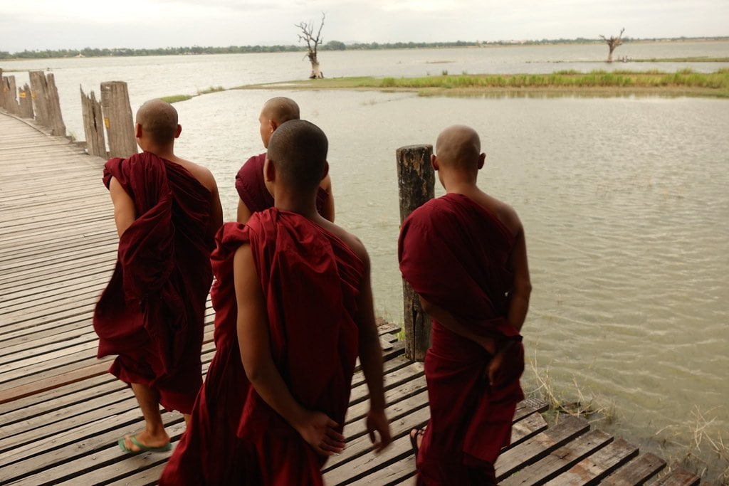 Four monks walking wooden bridge