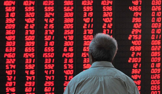 An investor looks at an electronic board showing the stock information at a brokerage house in Hefei