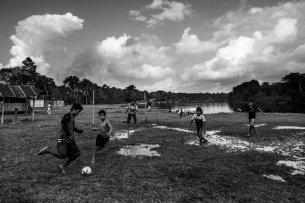 Un grupo de niños juega fútbol después de la lluvia.