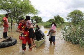 Bombero ayuda a niño a pisar tierra firme, luego de abandonar junto con sus padres la casa inundada.