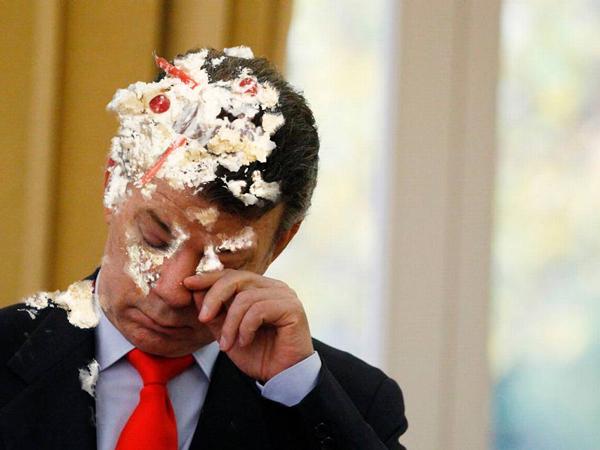 Juan Manuel santos limpia su cara después de recibir un pastelazo.