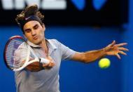 Roger Federer of Switzerland hits a return to Bernard Tomic of Australia during their men's singles match at the Australian Open tennis tournament in Melbourne