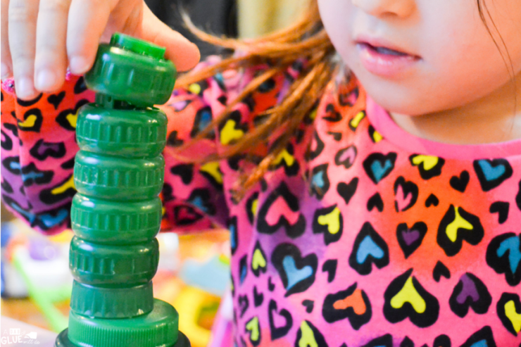 Challenge kids to a stacking challenge with leftover lids. Not only will they have fun trying to win, they can work on counting, numbers, and fine motor skills in the process. Stack a cap math activity is easy to put together, and can be adapted for preschool, kindergarten, or first grade.