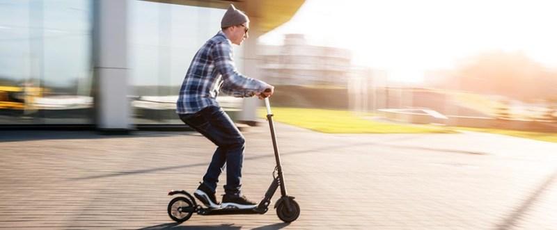 Elektroroller Elektro Roller ohne Helm junger Mann