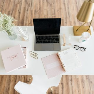 home office with pink notebooks and gray laptop