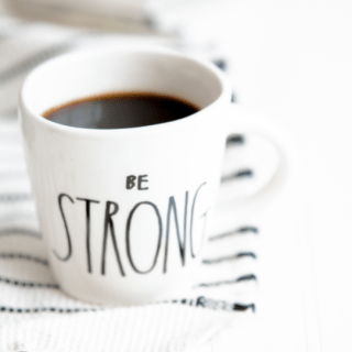 Coffee mug sitting on striped rug that says be strong.