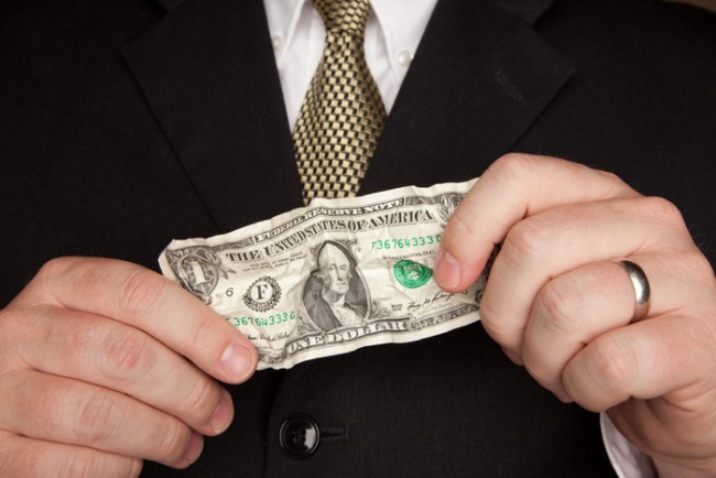 Businessman with Coat and Tie Holding Wrinkled United States Dollar Bill.