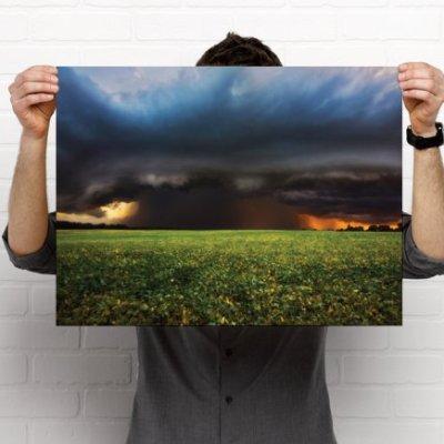 A supercell storm across a green farm field