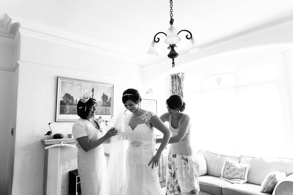 bride getting in wedding dress