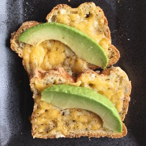 Two broiled cheese toasts with avocado slices on a plate