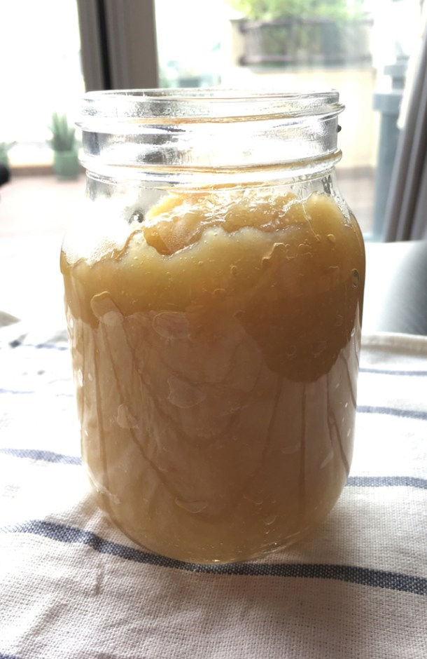 An open glass jar of Applesauce on a dish towel