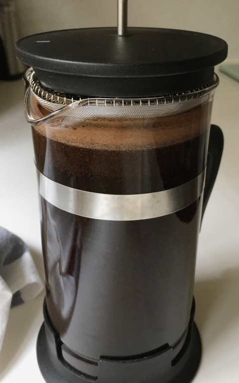 Coffee and water steeping in a French press carafe for Cold Brewed Coffee