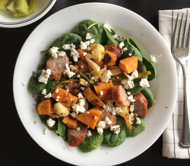 A round white plate with Roasted Veggie Sausage Salad containing spinach leaves, sausage, sweet potatoes,cauliflower, garlic, and feta cheese