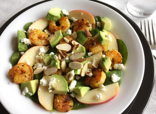 Turmeric Shrimp Spinach Salad on a white plate containing spinach, shrimp, apple slices, avocado, feta cheese, and sliced almonds