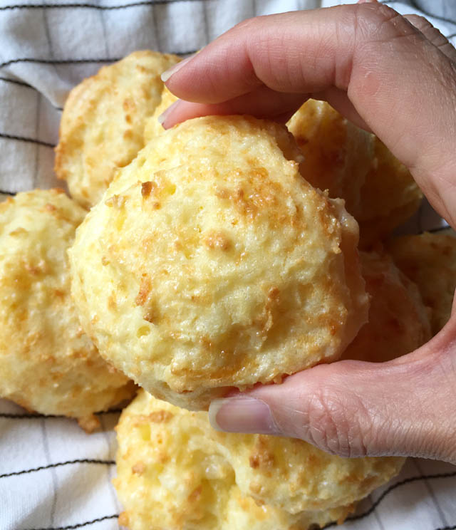 A hand holding a Brazilian cheese bread roll
