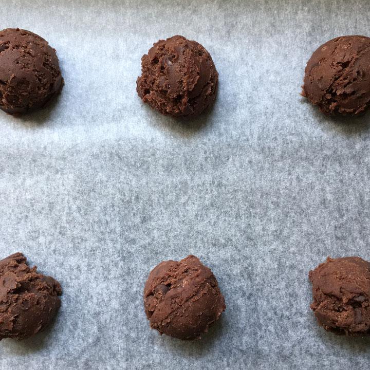 Six balls of brown cookie dough balls on a baking sheet