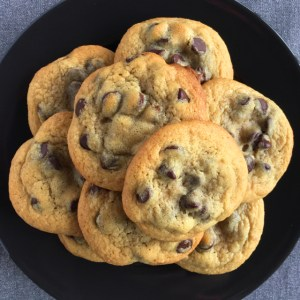 Several chocolate chip cookies on a black plate