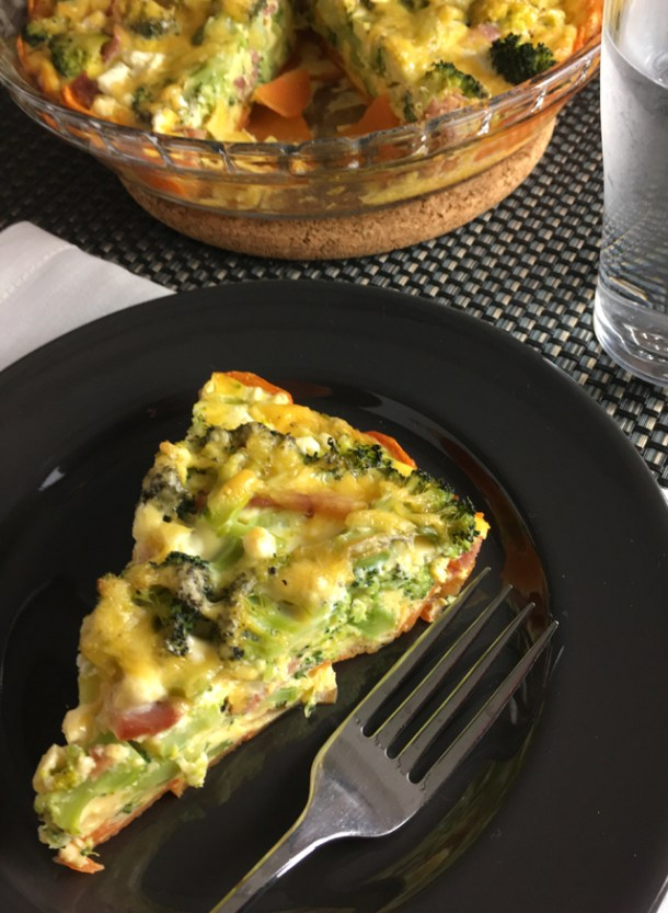 A piece of Sweet Potato Broccoli Bacon Quiche on a black plate with a fork