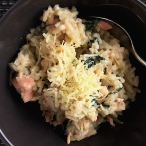 A bowl of salmon spinach risotto and a spoon