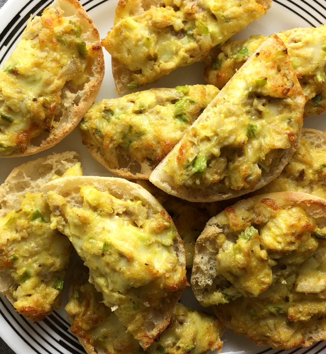 Curry Chicken Canapes made up of English muffins and curry chicken topping on a white plate