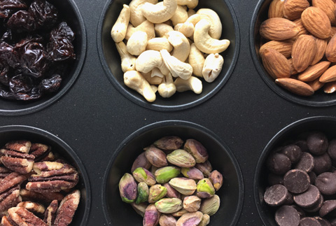 A muffin tin containing cranberries, cashews, almonds, pecans, pistachios, and chocolate chips for DIY Salty & Sweet Trail Mix