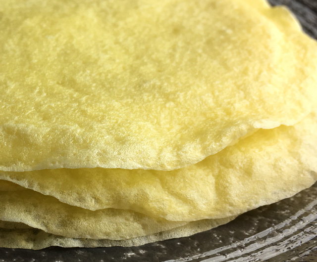 A stack of yellow Flourless Crepe Tortillas on a plate