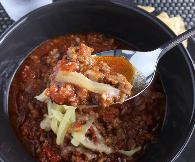 A spoonful of Chunky Chipotle Chili Con Carne with grated cheese