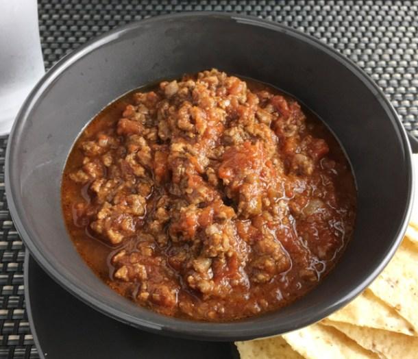 A dark grey bowl of Chunky Chipotle Chili Con Carne