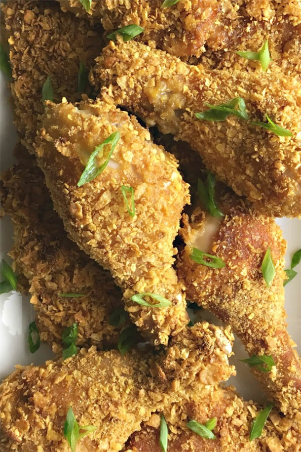 A white platter containing several pieces of cornflakes chicken sprinkled with chopped green onions