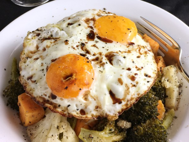 Two sunny-side up eggs over roasted vegetables with balsamic vinegar for Crispy Fried Eggs Over Veggies