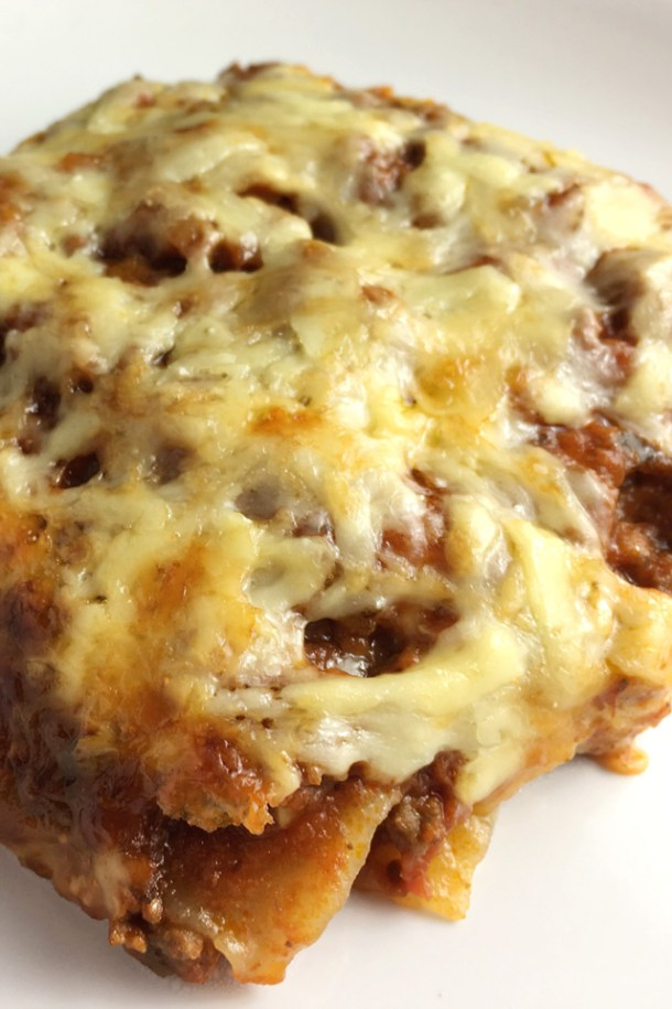 A closeup of a piece of Cheesy Bolognese Lasagna on a white plate