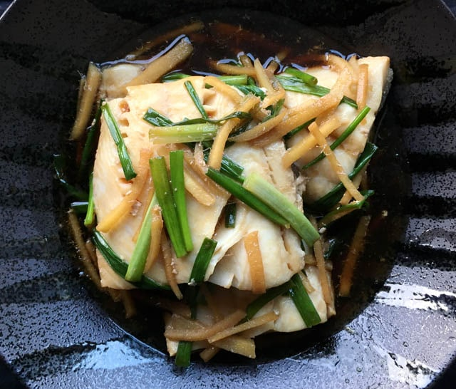 A black dish containing filets of fish and strips of green onion and ginger for poached black cod