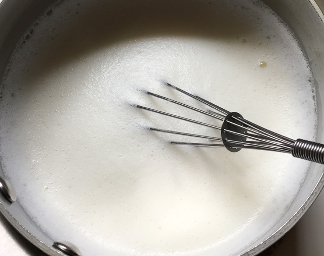 A metal whisk in frothy milk in a pot for English tea latte