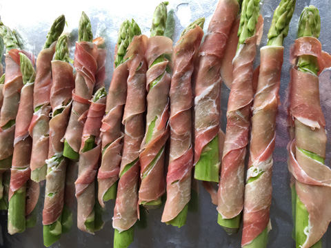 Uncooked Prosciutto Wrapped Asparagus on a baking sheet