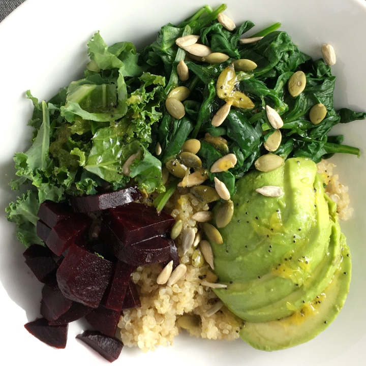 A white bowl containing beets, quinoa, avocado, spinach, kale, and seeds