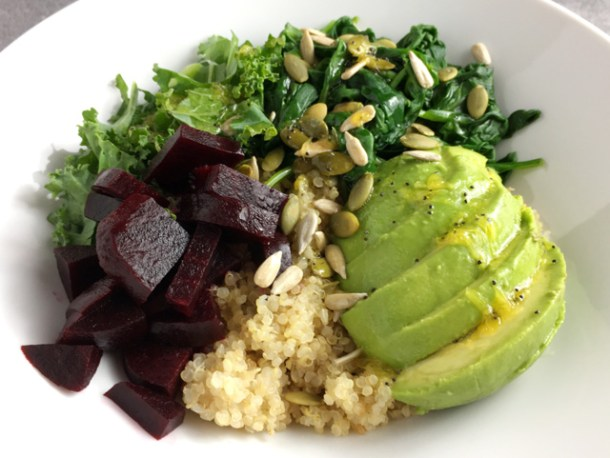 Super Food Quinoa Bowl in a white bowl containing quinoa, beets, kale, spinach, avocado, and sunflower and pumpkin seeds