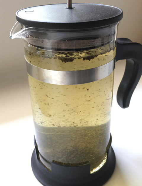 Water and loose tea leaves in a French press carafe for making Cold Brewed Tea