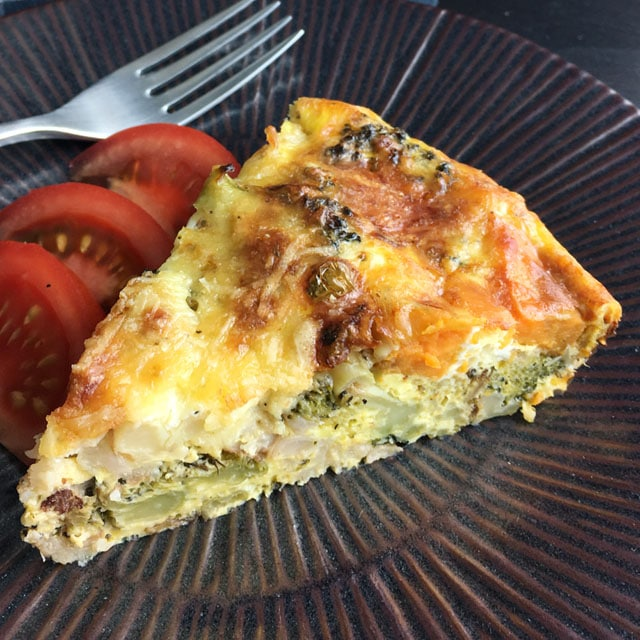 A triangular slice of roasted vegetable quiche on a round brown plate with red tomato wedges and a fork