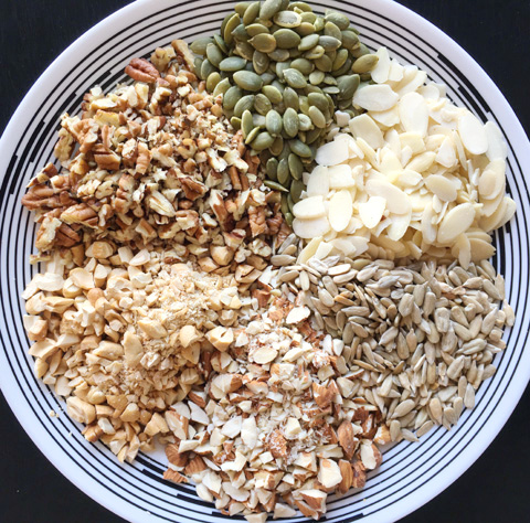 A white round plate containing pumpkin seeds, sunflower seeds, and chopped pecans, cashews, and almonds for Easy Grain Free Nutty Granola