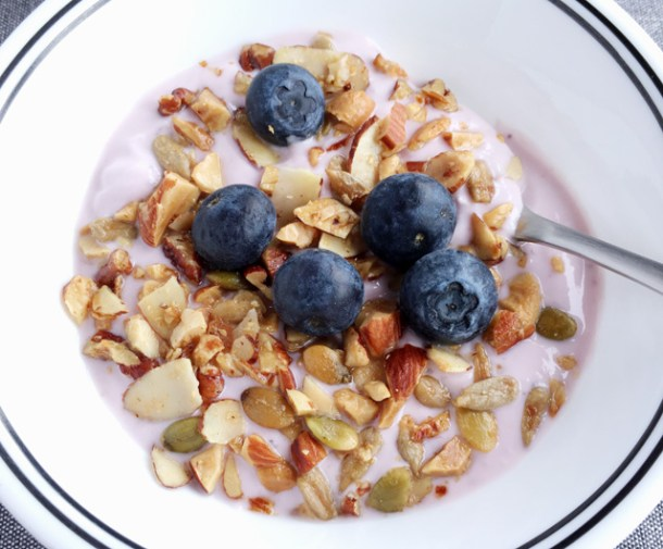 A white bowl containing Easy Grain Free Nutty Granola on yogurt with fresh blueberries