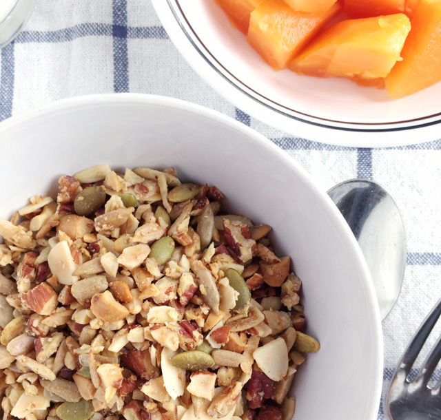 A bowl of Easy Grain Free Nutty Granola and a bowl of cut papaya